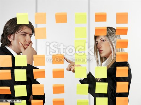Business team looking at adhesive notes on a transparent glass