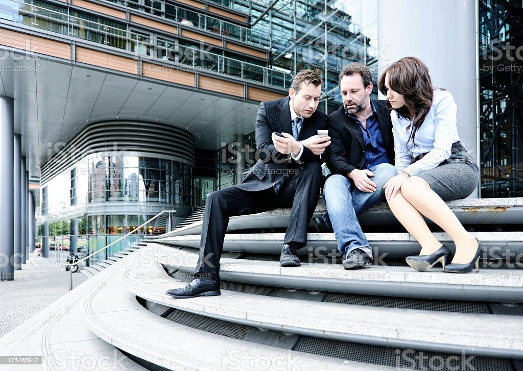 Equipe de negócios olhando para Smartphone sentado ao ar livre na escada - foto de acervo