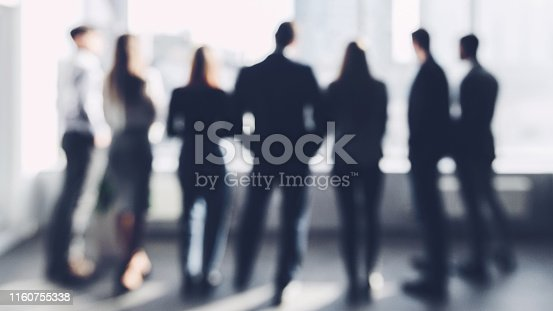 Business team concept, blurred. People looking through window, standing in row, back view