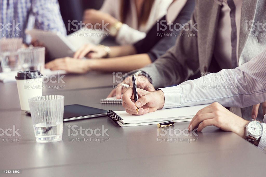 Business team meeting in an office Group of businessmen having meeting in a board room in an office, sitting at the conference table and writting notes. Close up of hands, unrecognizable people. 2015 Stock Photo