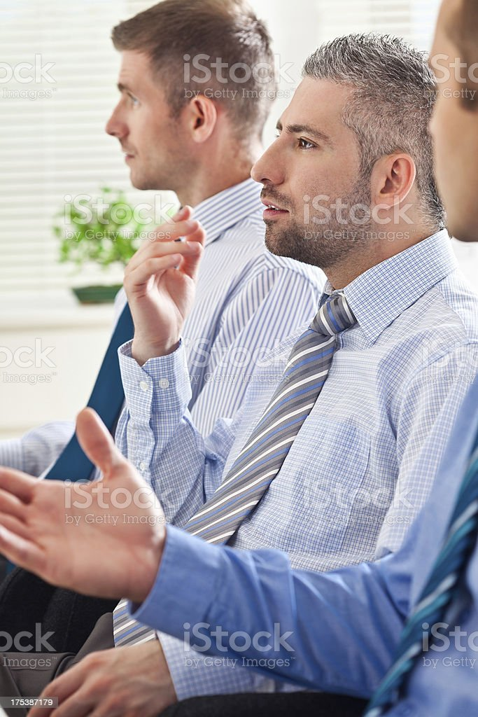 Business team meeting Three businessmen discussing in the office during seminar. A Helping Hand Stock Photo