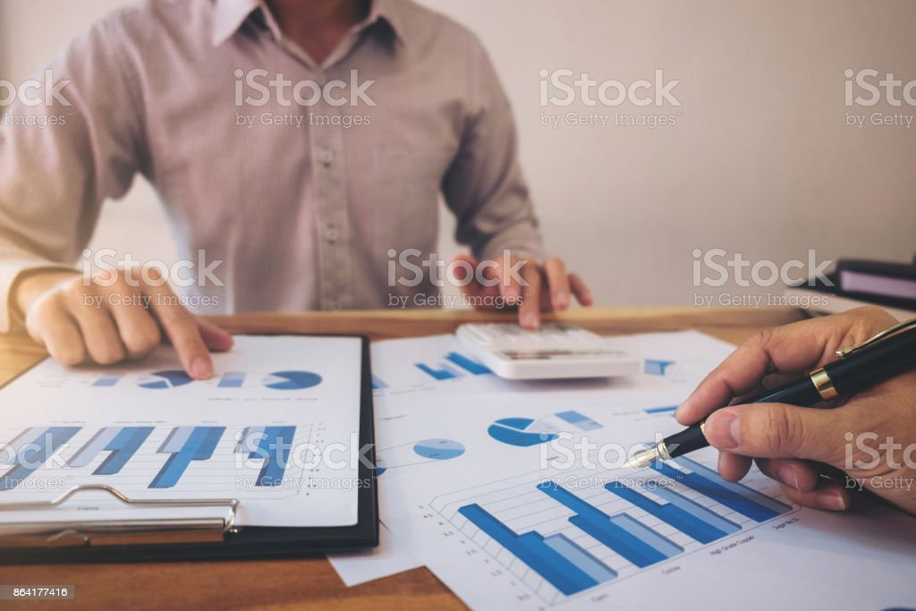 Business team meeting present, investor colleagues discussing new plan financial graph data on office table with laptop and calculator, Finance, accounting, investment royalty-free stock photo