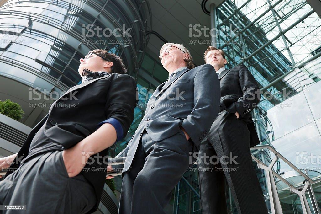 Equipe de negócios de três pessoas do lado de fora do edifício de escritório moderna - foto de acervo