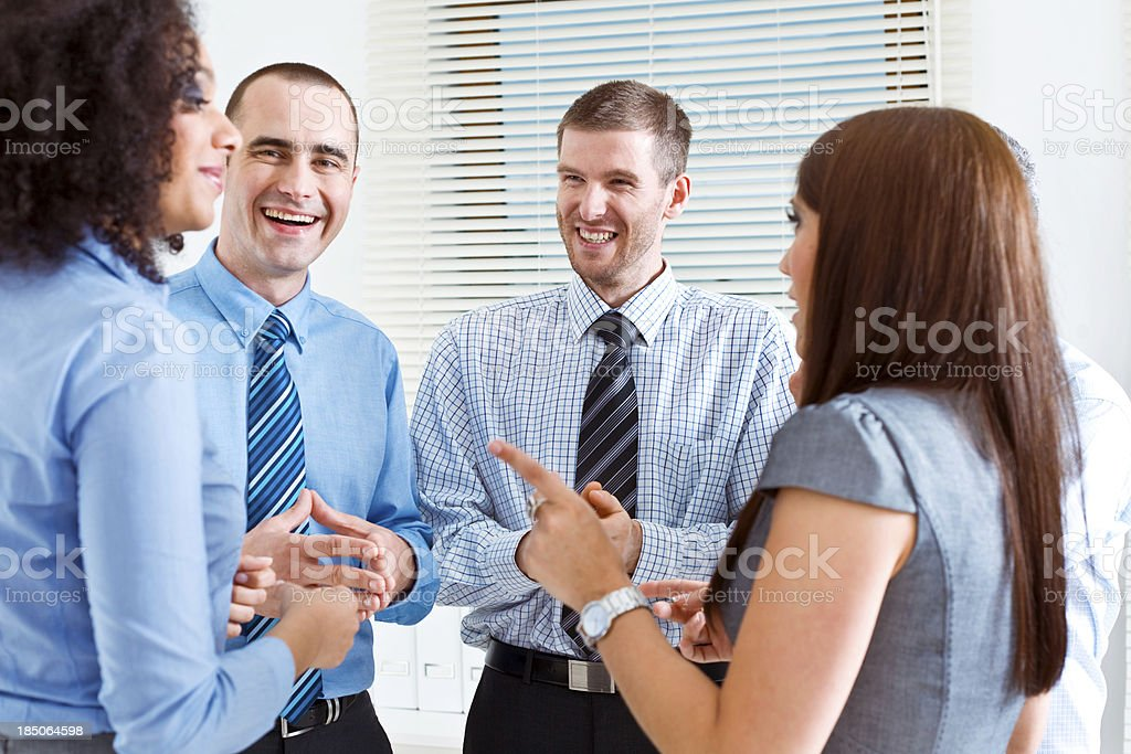 Business Team Five happy business people standing in an office and telling funny stories. 25-29 Years Stock Photo