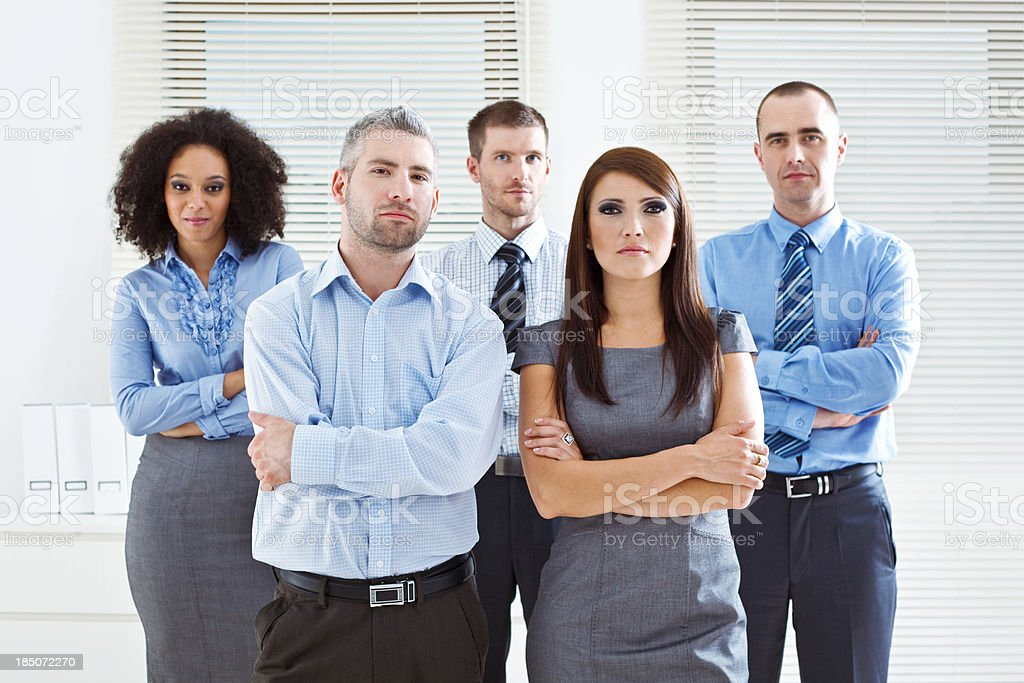 Business Team Portrait of five serious business people standing in two rows in an office. 25-29 Years Stock Photo