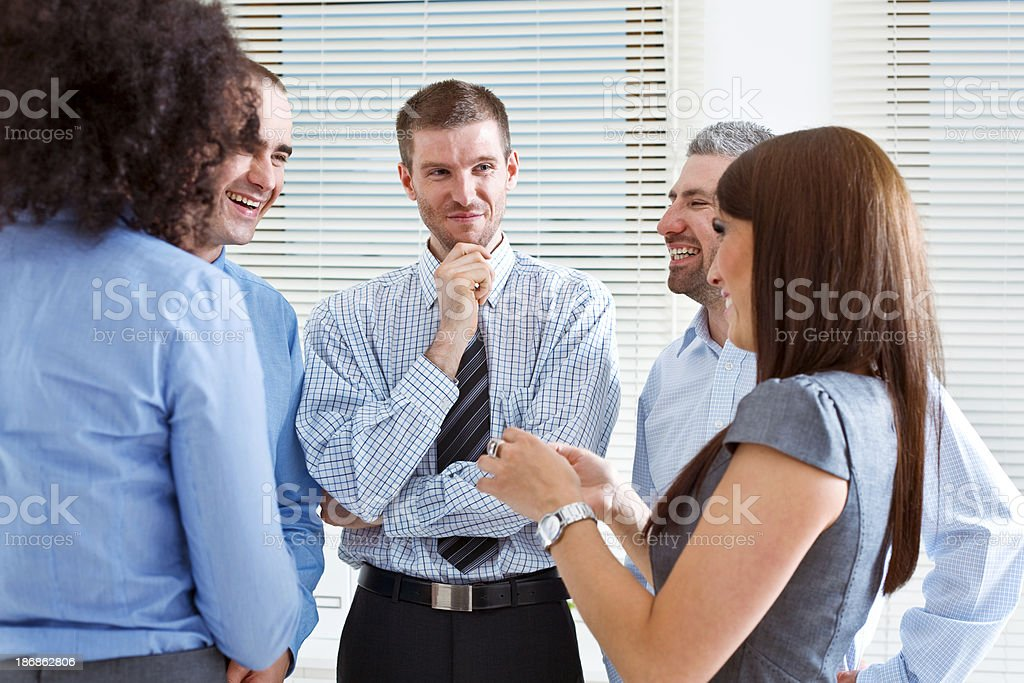Business Team Five smiling business people standing in an office and telling funny stories. 25-29 Years Stock Photo