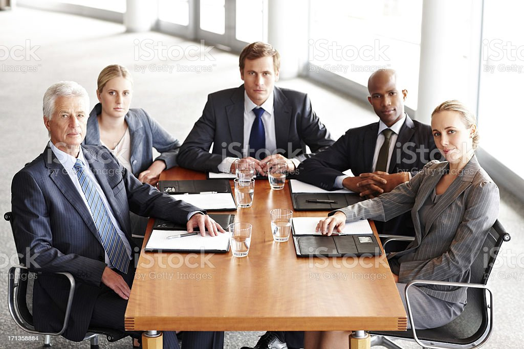 Diverse business team sit at a conference table and look towards the...