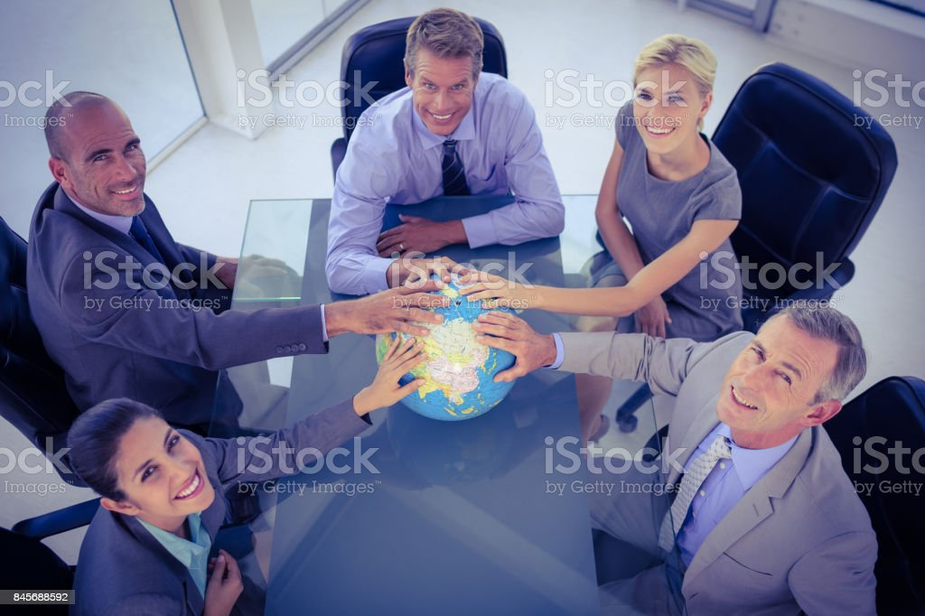 Business team putting hands on globe stock photo