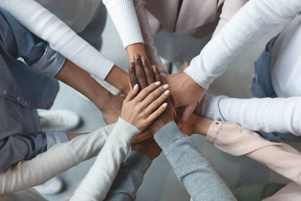 Business team putting hands together on top of each other stock photo