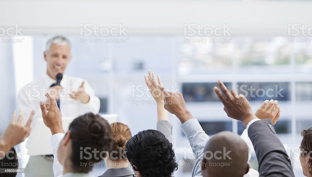 Business team raise their arms while watching a mature businessm stock photo