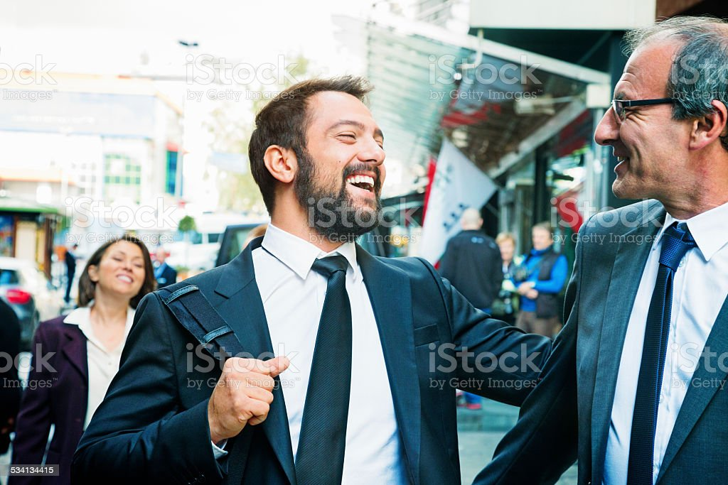 Business team reuniting near hotel with great excitement stock photo