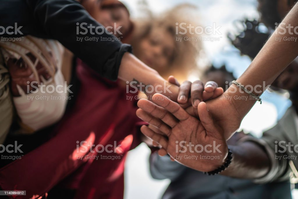 Business team showing unity with putting their hands together outdoors - Royalty-free 20-29 Years Stock Photo
