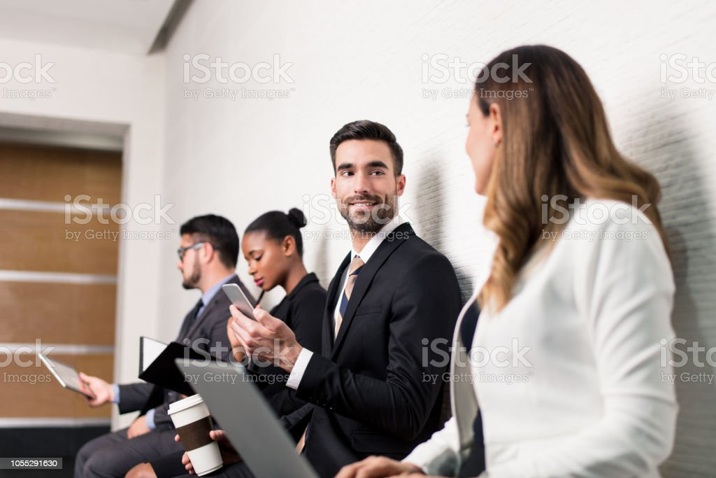 Business team sitting in waiting room and talking stock photo