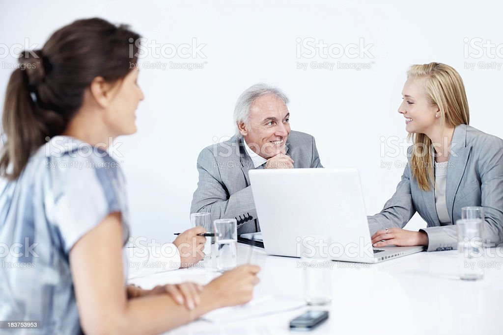 Business team smiling while working on laptop stock photo