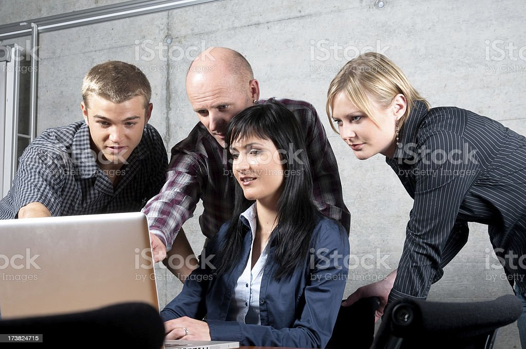 business team solving a problem together on laptop royalty-free stock photo