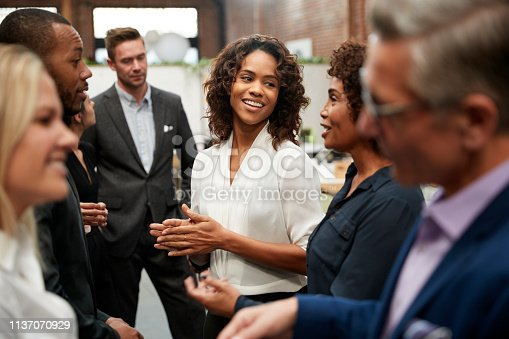 Business Team Standing Having Informal Meeting In Modern Office