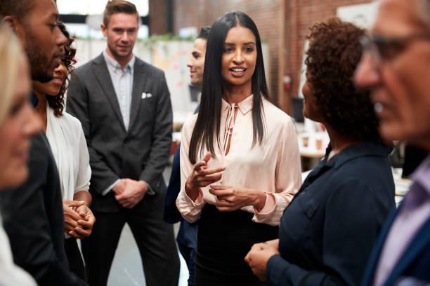 Equipo de negocios de pie con reunión informal en la oficina moderna - foto de stock