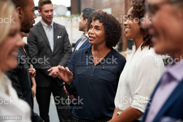 Business Team Standing Having Informal Meeting In Modern Office Stock Photo - Download Image Now