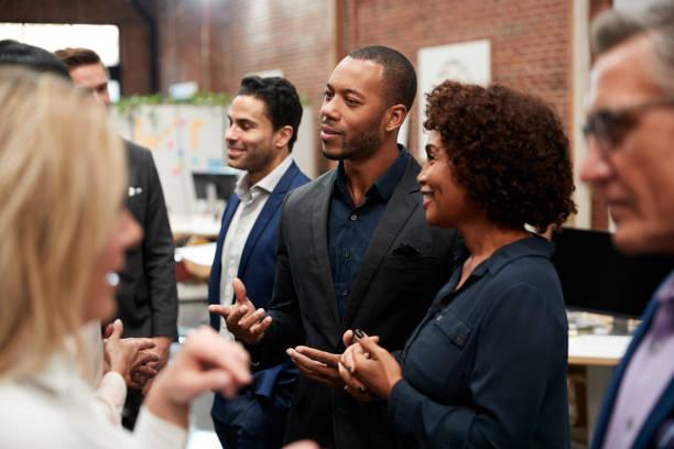 business team in piedi con riunione informale in ufficio moderno - evento foto e immagini stock
