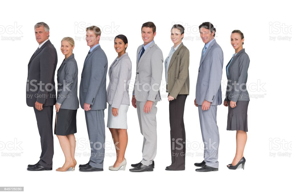 Business team standing in row and smiling at camera stock photo