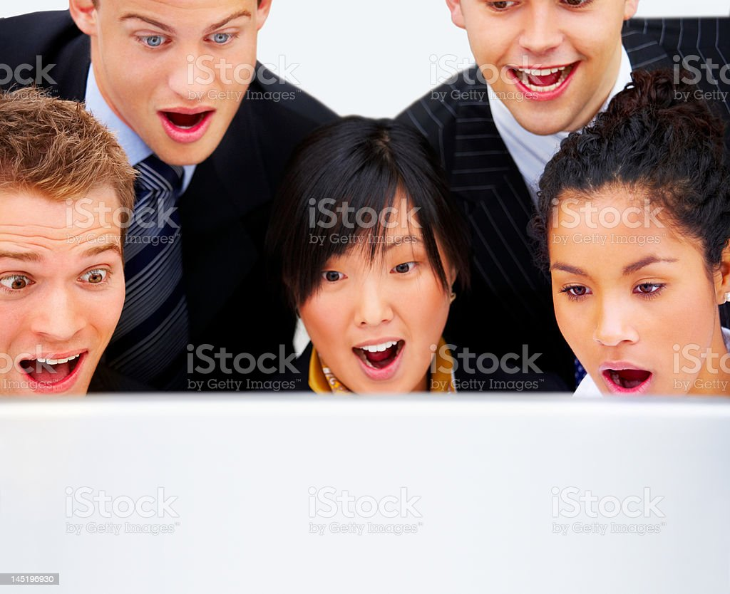 Business team staring at a computer screen in surprise royalty-free stock photo
