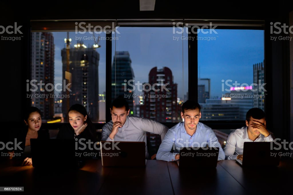 business team, three man and two woman working with computer overtime at night and low light stock photo