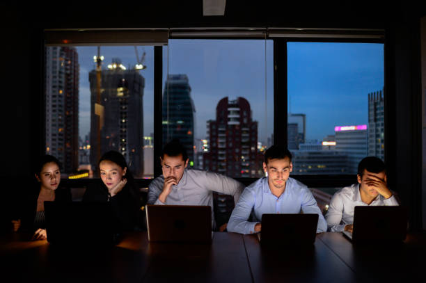 business team, three man and two woman working with computer overtime at night and low light - overworked stock pictures, royalty-free photos & images
