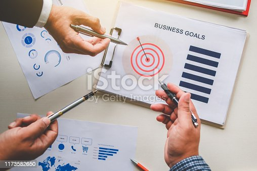 875531516istockphoto Business team together pointing to business goals, business goal concept 1173582650