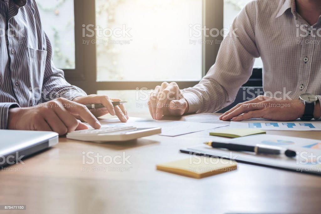 Business team two executive colleagues discussing and analysis working Financial investment on calculator with calculate on tablet Analyze business and market growth on financial document data graph stock photo