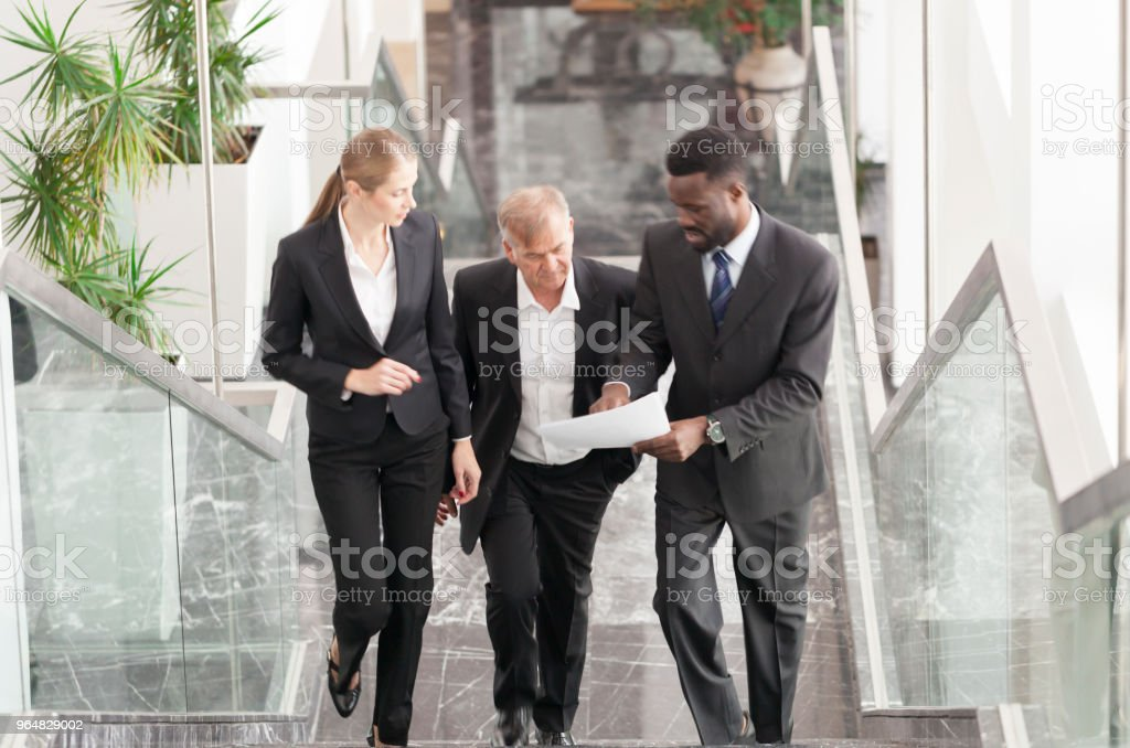 Business team updating senior manager while climbing the sraircase royalty-free stock photo
