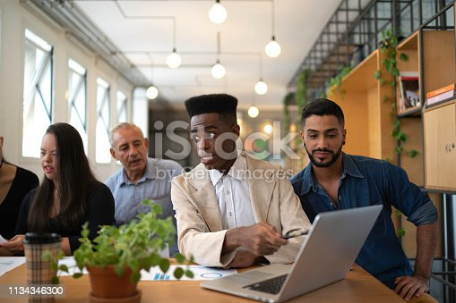 istock Business Team (including Special Needs Woman) using laptop on modern office 1134346300