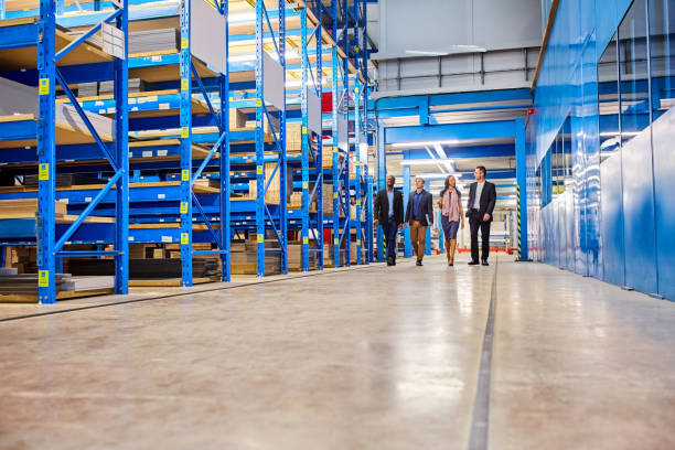 Business team walking together in warehouse stock photo