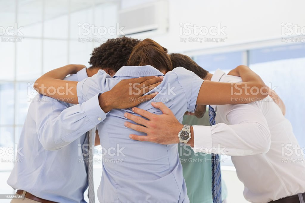 Business team with heads together forming a huddle stock photo