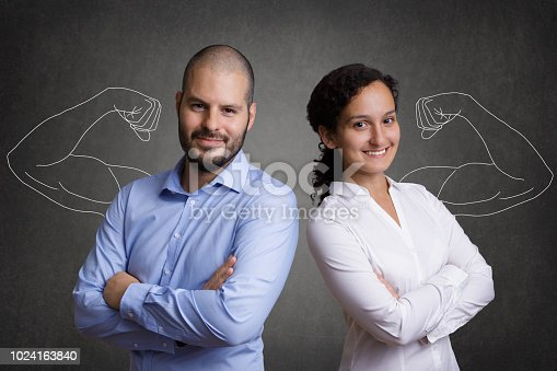 Business Team with muscular arms standing in front of a grey blackboard background. Concept of team-building and motivated young colleagues.