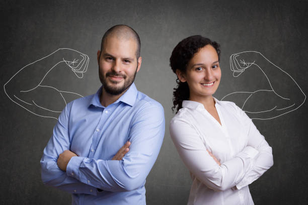 business team with muscular arms standing in front of a grey blackboard background - forza foto e immagini stock