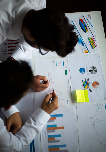 Business team working on graphs stock photo
