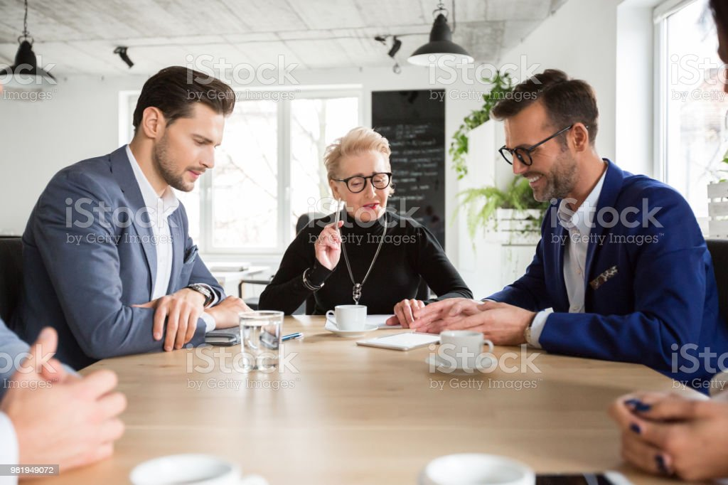 Business team working on new project proposal Business team working on new project proposal during meeting and looking at digital tablet. Group of business people having a meeting in office. Executives working together in boardroom. Active Seniors Stock Photo