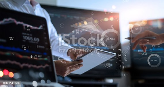 Business team working together. Businessman using tablet for analyzing data stock market in monitoring room with team pointing on the data presented in the chart on icon screen, forex trading graph, stock exchange trading online, financial investment concept. All on laptop screen are designed up.
