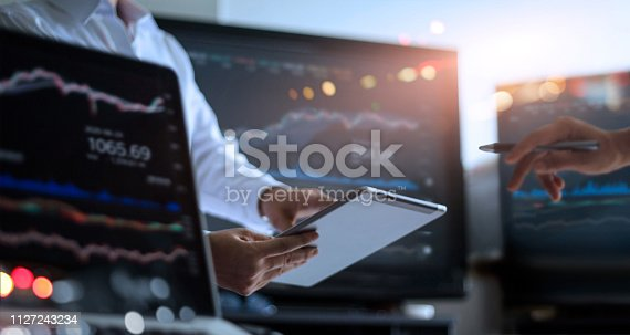 istock Business team working together. Businessman using tablet for analyzing data stock market in monitoring room with team pointing on the data presented in the chart on screen, forex trading graph, stock exchange trading online, financial investment concept. 1127243234