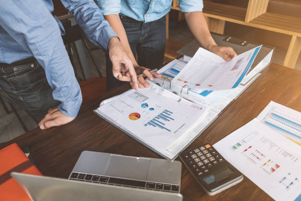 Business team working together discussing new plan financial graph data on office table, Business marketing concept stock photo