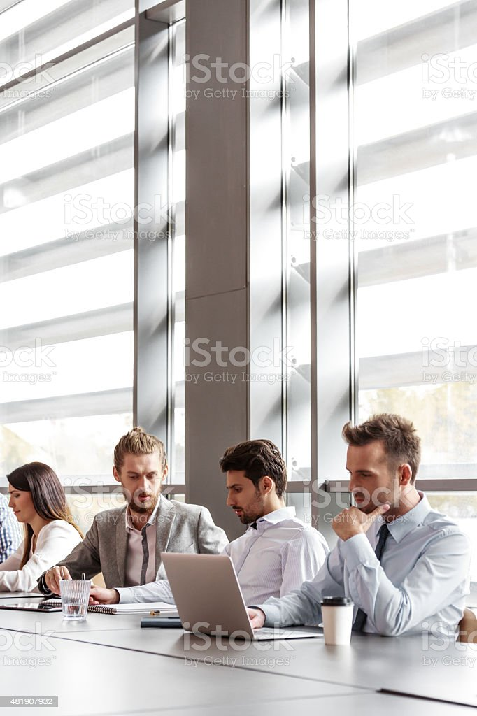 Business team working together in an office Group of business people - women and men - having meeting in a board room in an office, sitting at the table discussing, brainstorming, using laptop and collaborating. 2015 Stock Photo