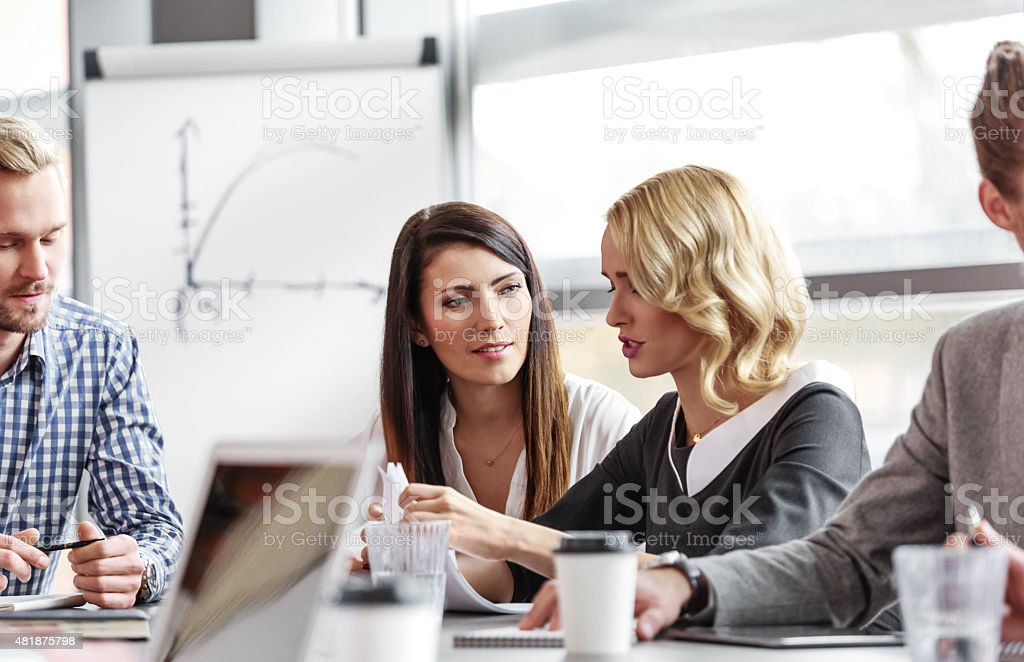 Business team working together in board room Group of business people - women and men - having meeting in a board room in an office, sitting at the table discussing new strategy of their company, brainstorming and collaborating. Focus on two businesswomen. 2015 Stock Photo
