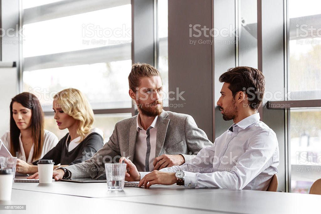Business team working together in board room Group of business people - women and men - having meeting in a board room in an office, sitting at the table discussing new strategy of their company, brainstorming and collaborating.   2015 Stock Photo