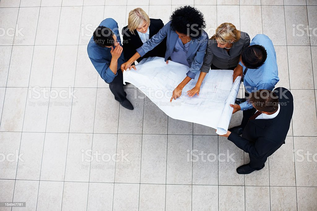 Business team working together on a blueprint royalty-free stock photo