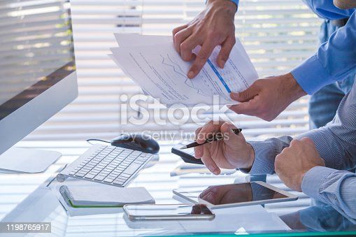 1068752548 istock photo Business team working together on financial analytics report. 1198765917