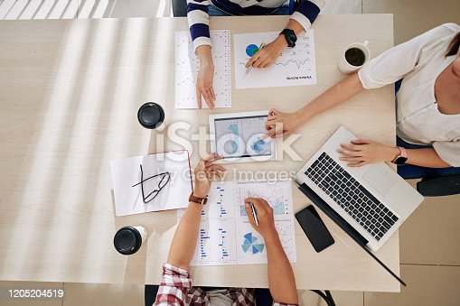 Business team sitting at big office table and discussing work and ways of company development when working with financial documents and reports