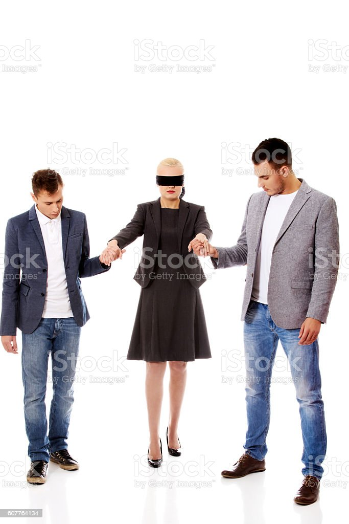 Business team-two men helping to blindfolded woman stock photo