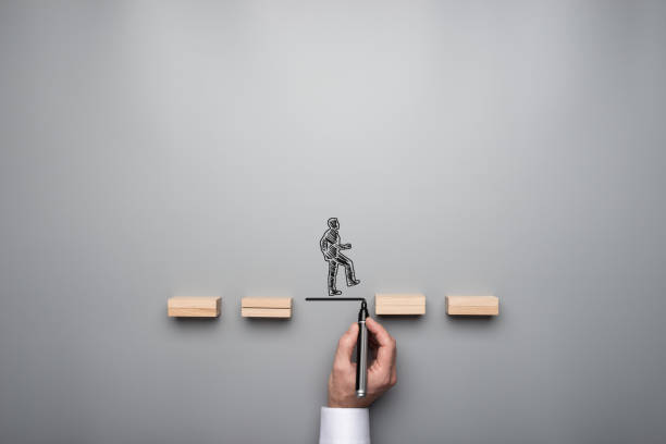 Business teamwork and cooperation concept Business teamwork and cooperation concept - silhouette of a businessman walking across wooden pegs with other businessman drawing the missing step for his colleauge. single step stock pictures, royalty-free photos & images