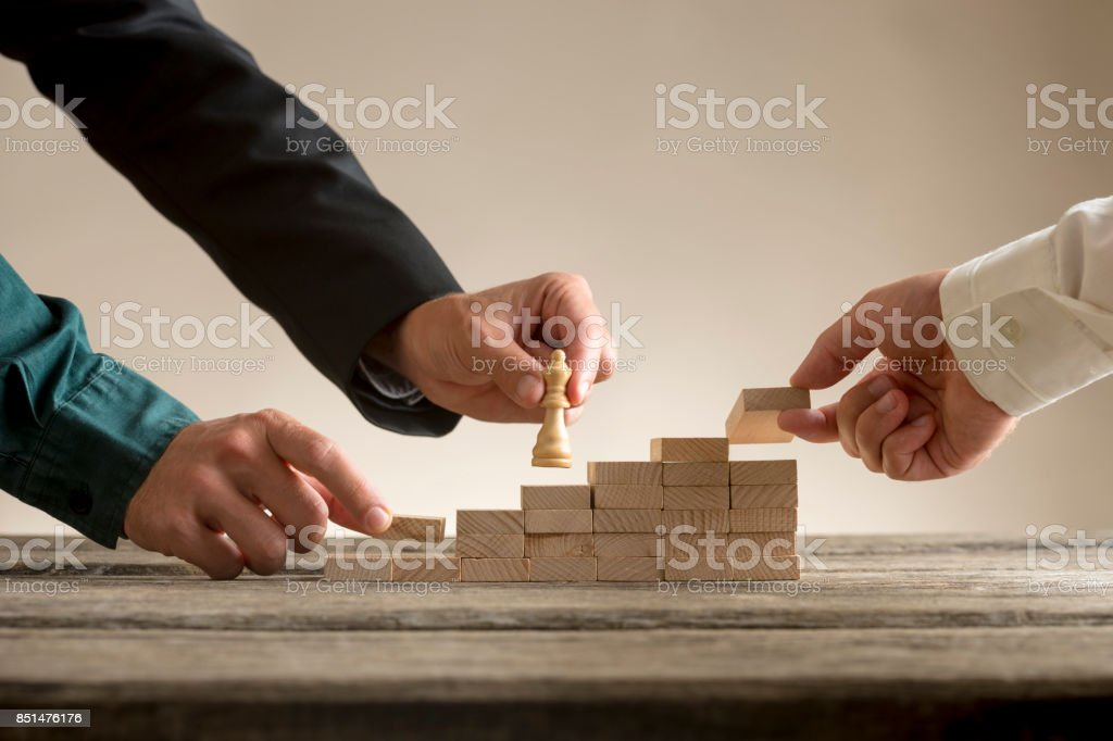 Business teamwork concept with a businessman moving a chess piece up a series of steps stock photo