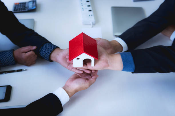 Business teamwork holding a house with Discussion a real estate agent at the office. property for sale concept. Teamwork successful meeting workplace strategy. stock photo